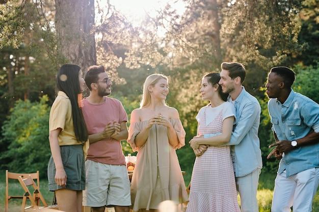 Gesellschaft von drei glücklichen jungen paaren in freizeitkleidung, die über neuigkeiten oder ihre pläne für den sommer diskutieren, während sie sich im park versammeln