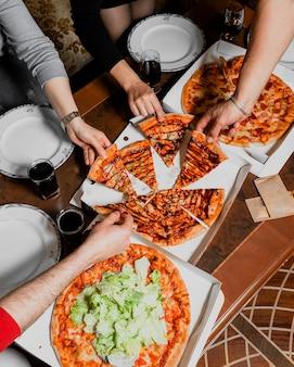 Gesellschaft von freunden, die pizza essen und reden