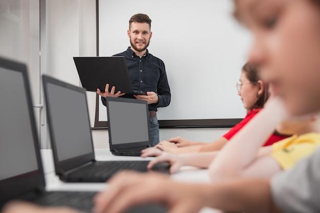 Gesellschaft von kindern, die während des unterrichts laptops benutzen