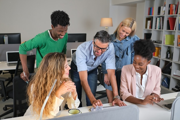 Gesellschaft von multiethnischen kollegen, die sich am tisch im büro versammeln