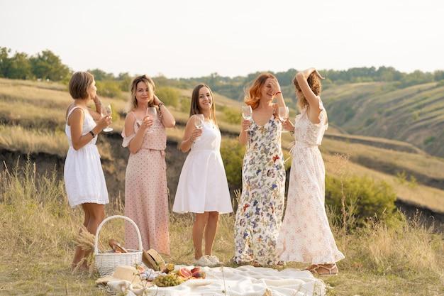 Gesellschaft von wunderschönen freundinnen, die spaß haben und ein sommergrünes picknick genießen, tanzen und alkohol trinken. menschen-konzept.