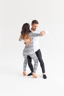 Gesellschaftstanz, bachata, kizomba, zouk, tangokonzept - mann umarmt frau, während er über weiße wand mit kopierraum tanzt