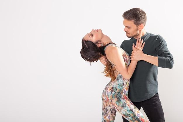 Gesellschaftstanz, bachata, salsa, kizomba, zouk, tangokonzept - mann umarmt frau, während er über weiße wand mit kopienraum tanzt