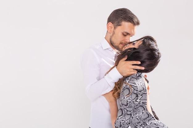 Gesellschaftstanz, kizomba, tango, salsa, menschenkonzept - schönes paar, das bachata auf weißer wand tanzt