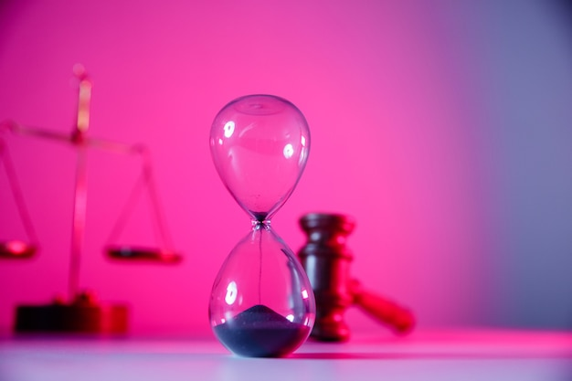 Gesetz und gerechtigkeit konzept sanduhrwaage und hölzerner richterhammer in rosa neon-nahaufnahme