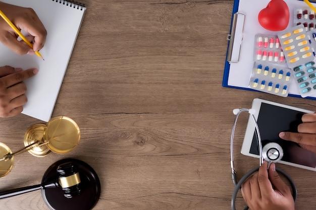Gesetz und klinische elemente auf einem schreibtisch, während menschen die objekte benutzen