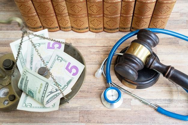 Gesetzeshammer und balancegewichter mit geld, behandlungskosten und medizinrechtlichem konzept