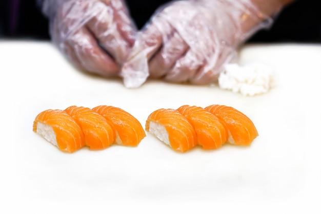 Gesetzter japanischer küchenchef der lachssushi, der auf weißer tabelle kocht.