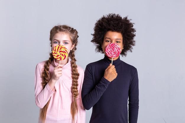 Gesicht bedecken. süße, gut aussehende kinder, die süßigkeiten halten und die hälfte des gesichts bedecken, während sie als fotomodelle arbeiten