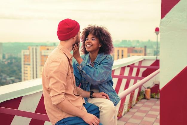 Gesicht berühren. fröhliche emotionale junge frau, die lächelt, während sie mit ihrem freund auf dem dach sitzt und sein gesicht berührt