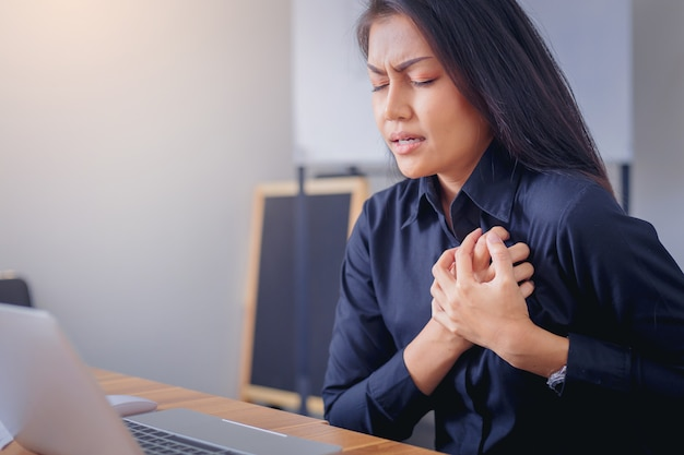 Gesicht der berufstätigen frau, das brust wegen des herzinfarkts im büro leidet und hält