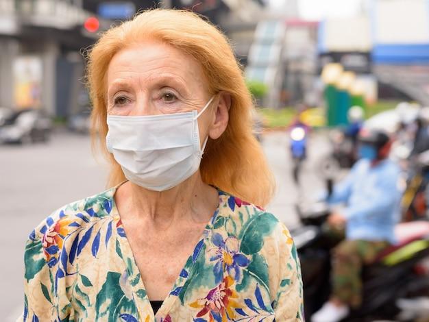 Gesicht der blonden älteren frau mit maske, die in der stadt draußen denkt