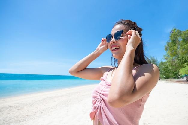 Gesicht der glücklichen jungen frau mit rosa panzer, die sonnenbrille trägt und hält. glückliche frau, die während der sommerferien auf see lächelt. schöne dame, die am strand entspannt. frischer himmel.