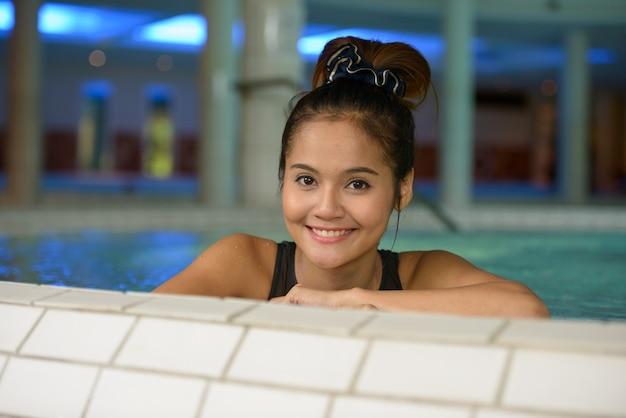 Gesicht der glücklichen jungen schönen asiatischen touristenfrau, die am spa entspannt