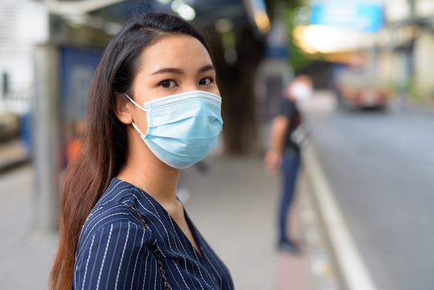 Gesicht der jungen asiatischen geschäftsfrau mit maske zum schutz vor ausbruch des koronavirus, die an der bushaltestelle wartet