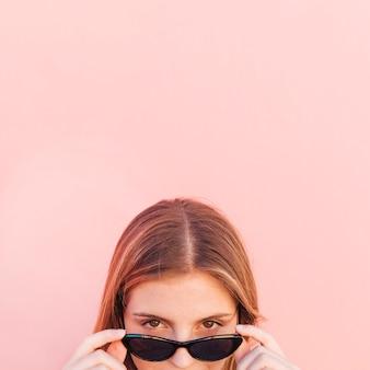 Gesicht der jungen frau, das durch schwarze sonnenbrille gegen rosa hintergrund späht