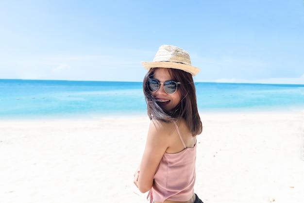 Gesicht der jungen frau, die rosa tankstrohhut trägt, der sonnenbrille trägt. glückliche frau, die während der sommerferien auf see lächelt. schöne dame, die am strand entspannt.