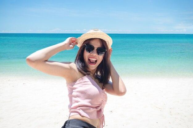 Gesicht der jungen frau mit brille und hut am strand