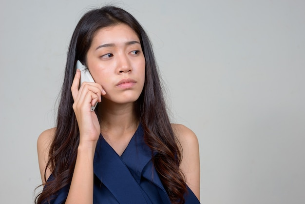 Gesicht der jungen schönen asiatischen geschäftsfrau, die beim telefonieren denkt