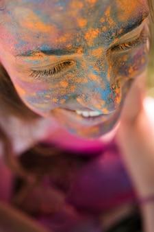 Gesicht der lächelnden frau mit blauem und gelbem holi pulver
