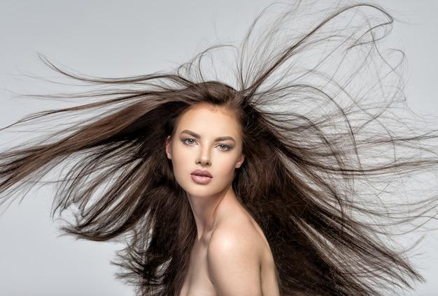Gesicht der schönen frau mit dem langen braunen haar, das im studio aufwirft