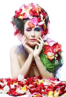 Gesicht der schönen frau und rosafarbene blumenblätter