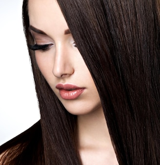 Gesicht der schönen jungen frau mit braunem make-up und glattem haar