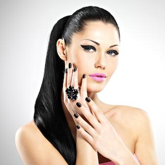 Gesicht der schönen sexy frau mit schwarzen nägeln und rosa lippen. sexy mädchen mit mode make-up