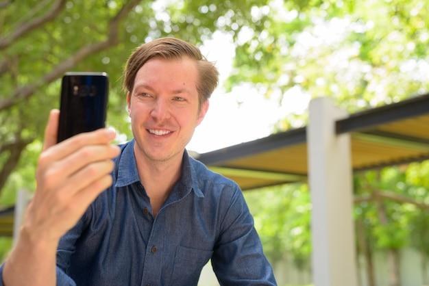 Gesicht des glücklichen jungen hübschen blonden geschäftsmannes, der selfie am park draußen nimmt