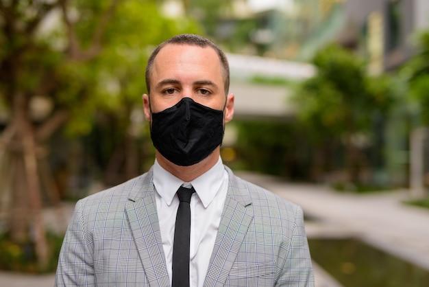Gesicht des hispanischen kahlen geschäftsmannes, der maske zum schutz vor dem ausbruch des koronavirus in der stadt mit der natur trägt