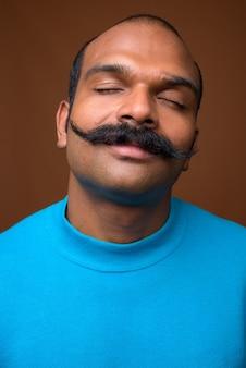 Gesicht des indischen mannes mit schnurrbart, der blauen pullover trägt