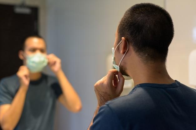 Gesicht des jungen asiatischen mannes, der maske zum schutz vor coronavirus-ausbruch im badezimmer trägt