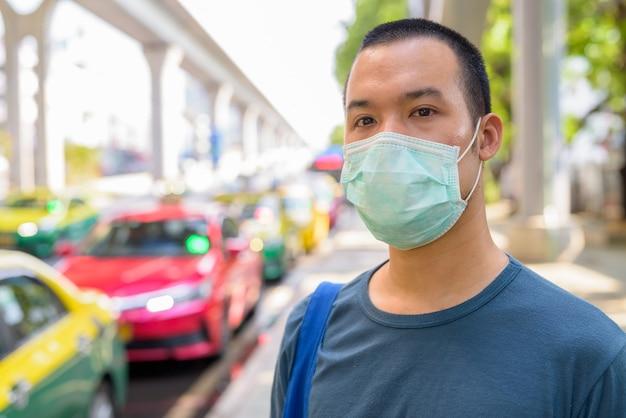 Gesicht des jungen asiatischen mannes mit maske zum schutz vor coronavirus-ausbruch an der taxistation in der stadt