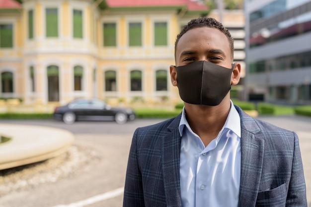 Gesicht des jungen geschäftsmannes, der maske zum schutz vor ausbruch des koronavirus in der stadt trägt