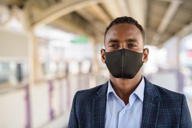 Gesicht des jungen geschäftsmannes im anzug mit maske zum schutz vor ausbruch des koronavirus am himmelbahnhof