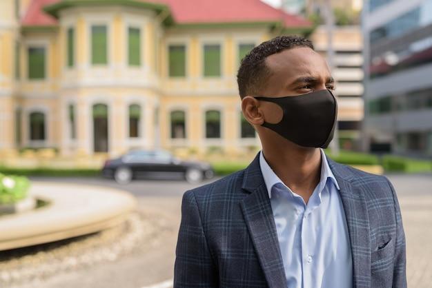 Gesicht des jungen geschäftsmannes mit maske zum schutz vor dem ausbruch des koronavirus, der draußen denkt