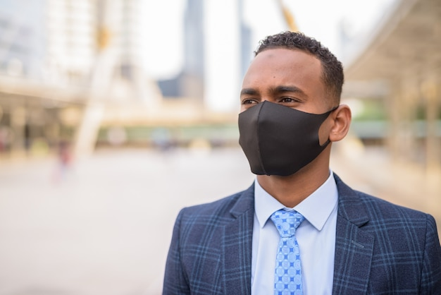 Gesicht des jungen geschäftsmannes mit maske zum schutz vor dem ausbruch des koronavirus in der stadt denkend