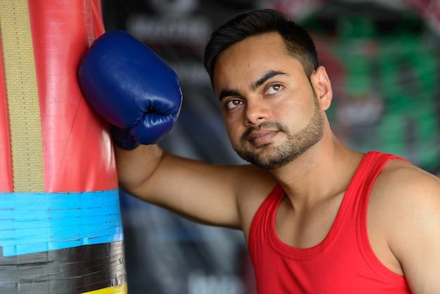 Gesicht des jungen gutaussehenden bärtigen indischen mannes als boxer, der an der turnhalle denkt
