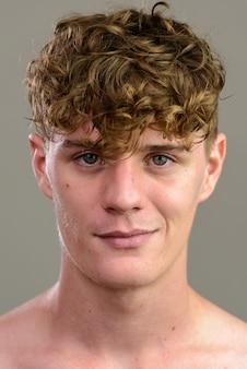 Gesicht des jungen gutaussehenden mannes mit dem lockigen blonden haar ohne hemd