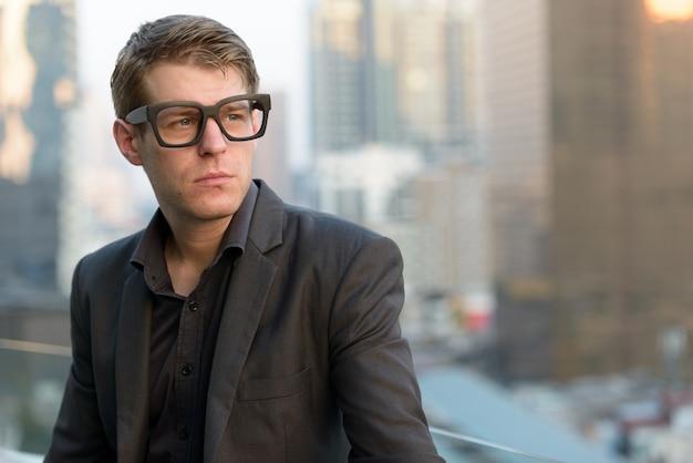 Gesicht des jungen gutaussehenden nerd-geschäftsmannes mit brillen, die in der stadt denken