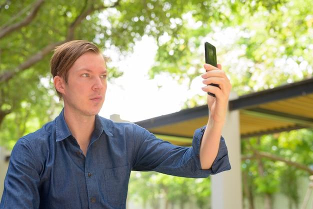 Gesicht des jungen hübschen blonden geschäftsmannes, der selfie am park draußen nimmt