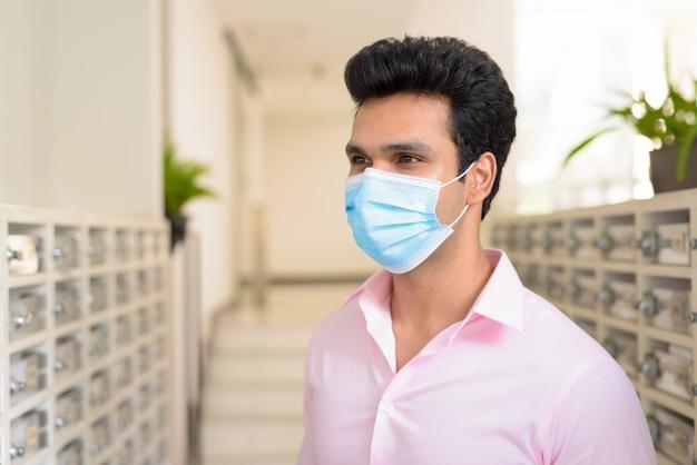 Gesicht des jungen indischen geschäftsmannes, der maske beim überprüfen des briefkastens trägt