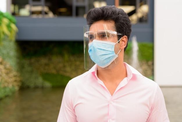Gesicht des jungen indischen geschäftsmannes mit maske und gesichtsschutz, die in der stadt draußen denken
