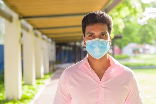 Gesicht des jungen indischen geschäftsmannes mit maske zum schutz vor dem ausbruch des koronavirus im park