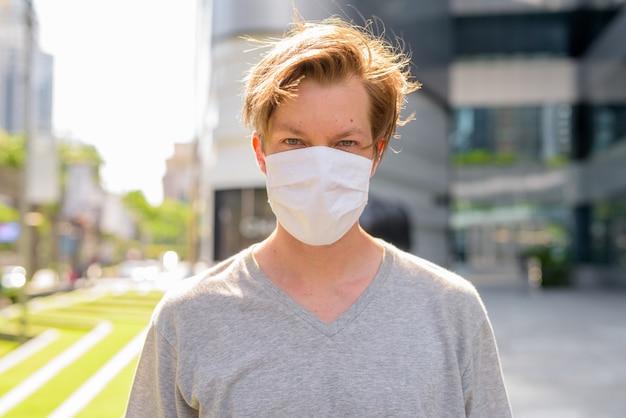 Gesicht des jungen mannes, der maske zum schutz vor coronavirus-ausbruch im freien trägt