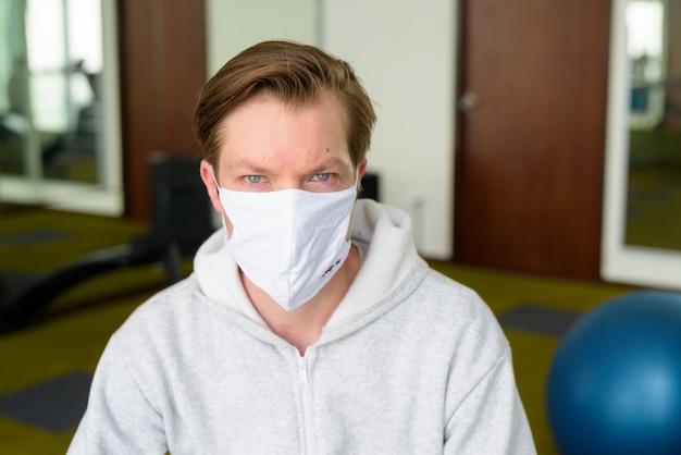 Gesicht des jungen mannes mit maske, die an der turnhalle sitzt