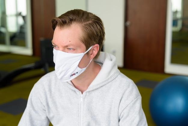 Gesicht des jungen mannes mit maske, die im fitnessstudio denkt und sitzt
