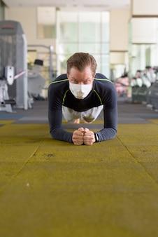 Gesicht des jungen mannes mit maske, die plankenposition auf dem boden im fitnessstudio während coronavirus covid-19 tut