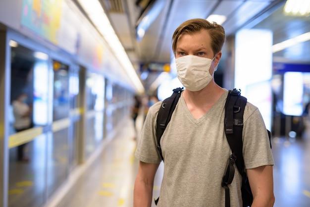 Gesicht des jungen mannes mit maske zum schutz vor dem ausbruch des coronavirus, der am u-bahn-bahnhof wartet