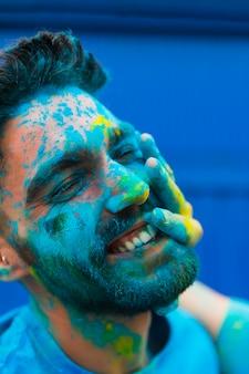 Gesicht des mannes befleckte blaues pulver auf holi-festival